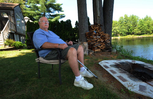 Arthur Green sits in a chair on his front lawn like he has for years, watching a pair of loons play in Sanborn Pond in Brooks on Tuesday, July 31, 2012. Green almost lost his property to unscrupulous relatives, including the granddaughter he says he helped raise.