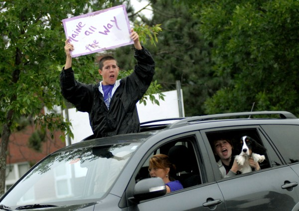 Will Huston, 16, of Hampden, holds a sign out of a car for the Maine District 3 team on his way in to the opening ceremony of the 2012 Senior League World Series at Mansfield Stadium Saturday night.
