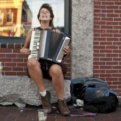 "Josie English plays accordian on Commercial Street while her traveling companion, Rosie, rests at her side Sunday, Aug. 26, 2012, in Portland. ""I enjoy playing on the street because I get to meet a lot of cool people. But it gets really frustrating; people just really don''t care, they''re wrapped up [in their own world], even if I sound good they just see my whole appearance and they''re like, 'you''re probably one of those dirty, traveling people, I don''t want to give you money because you''re probably going to spend it on booze or drugs,'"" she said."