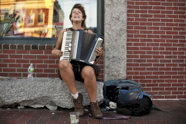 Josie English plays accordian on Commercial Street while her traveling companion, Rosie, rests at her side Sunday, Aug. 26, 2012, in Portland. &quotI enjoy playing on the street because I get to meet a lot of cool people. But it gets really frustrating; people just really don''t care, they''re wrapped up [in their own world], even if I sound good they just see my whole appearance and they''re like, 'you''re probably one of those dirty, traveling people, I don''t want to give you money because you''re probably going to spend it on booze or drugs,'&quot she said.