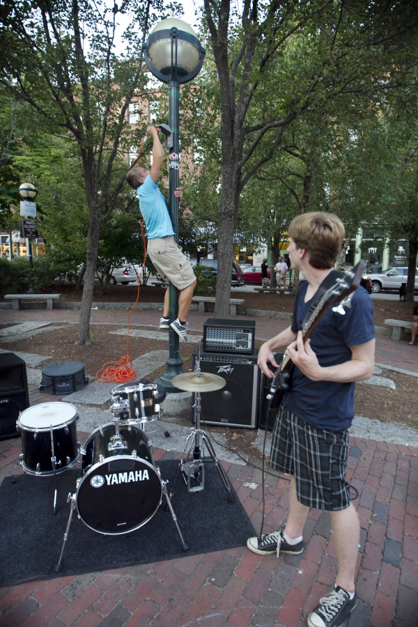 Sam Hansen of the funk band Powerhouse Road, climbs a light post to plug in an unsuccessful search for electricity in Tommy's Park on Sunday, Aug. 26, 2012, in Portland. A policeman later told bass player Conor McGrory (right) that the city recently turned off the power after complaints about a loud, techno-music performer.