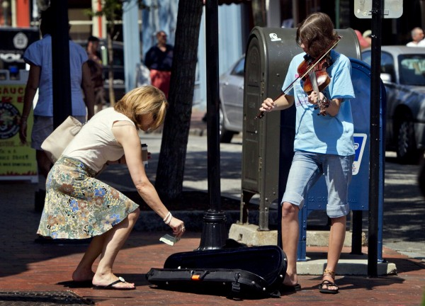 Cecilia Howard, 13, of South Portland receives a tip while fiddling on Exchange Street on Sunday, Aug. 26, 2012, in Portland. The ninth-grader says the best tips come when a cruise ship is in town. The worst is during a Friday night Art Walk. &quotIt's too crowded,&quot she said.