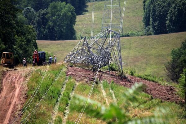 Workers examine one of three power transmission towers toppled by high winds near Ellenboro, W.Va., on June 29, 2012, shortly before the same wind storm swept through the Washington region.