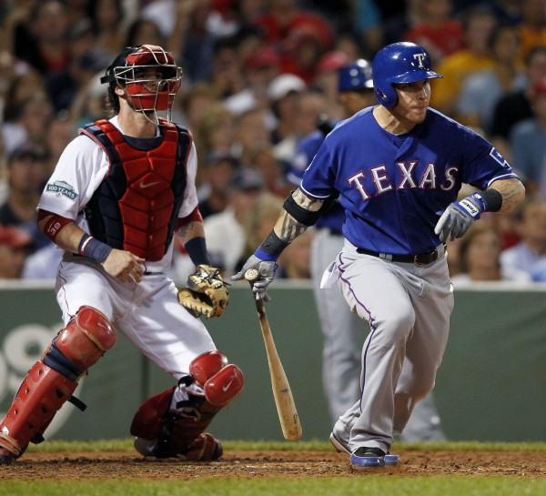 Texas Rangers' Josh Hamilton follows through on an RBI single in front of Boston Red Sox's Jarrod Saltalamacchia in the sixth inning of a baseball game in Boston, Tuesday night, Aug. 7, 2012.