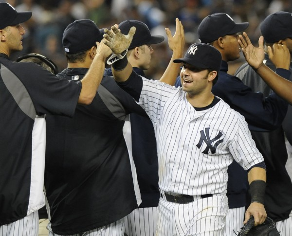 New York Yankees' Nick Swisher high five with teammates after the Yankees beat the Boston Red Sox 6-4 in a baseball game on Friday, Aug., 17, 2012, at Yankee Stadium in New York. Swisher hit two solo home runs during the game.