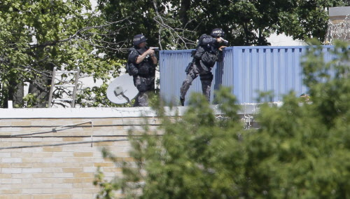 Armed police investigate the Sikh Temple in Oak Creek, Wis. where a shooting took place on Sunday, Aug. 5, 2012.