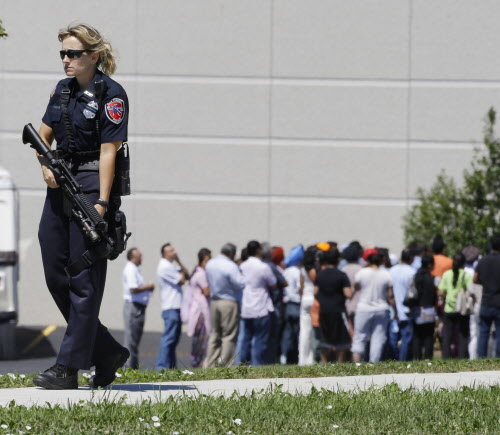Police stand guard as bystanders watch at the scene of a shooting inside a Sikh temple in Oak Creek, Wis., on Sunday, Aug. 5, 2012. Police and witnesses describe a chaotic situation with an unknown number of victims, suspects and possible hostages.
