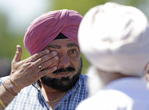 A man wipes away tears outside the Sikh Temple in Oak Creek, Wis. where a shooting took place on Sunday, Aug 5, 2012.
