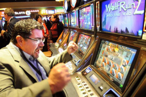 John Morrison of Lewiston reacts as the slot machine he is playing racks up points at Oxford Casino recently.