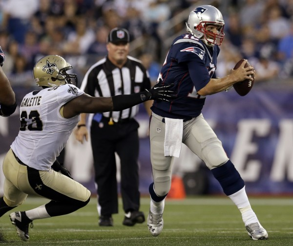 New England Patriots quarterback Tom Brady (12) evades the grasp of New Orleans Saints defensive end Junior Galette (93) during their first NFL preseason game in Foxborough, Mass., Thursday, Aug. 9, 2012.
