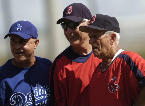 Los Angeles Dodgers bench coach Dave Jauss (left), Boston Red Sox minor league talent coordinator Dick Berardino and Red Sox instructor and former player Johnny Pesky react to fans as their teams warm up for a spring training game in March 2006.