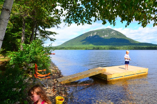 A little boy fishes from a float at a Moosehead Lake Region sporting camp.