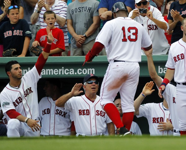 Boston Red Sox's Carl Crawford (13) is welcomed to the dugout by manager Bobby Valentine, bottom center, after he was brought home on a two-run home run by Adrian Gonzalez in the fifth inning of a baseball game against the Minnesota Twins at Fenway Park, in Boston, Sunday, Aug. 5, 2012.