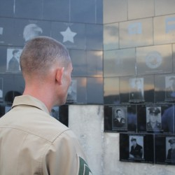 A soldier looks into the black granite tiles that cover the Midcoast Area Veterans Memorial on Limerock Street on Friday night, after the dedication ceremony. The memorial took 16 years to erect.