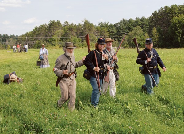 Confederate soldiers Corp. Tomm Bassford of Salem (left) and 1st Sgt. Pat Canavan of Newton, Mass. (third from left) escort captured Union soldiers Pvt. Deborah Lipsky of Linneus (second from left) and Corp. Tom Nelson of Poland Spring from the battlefield at Good Will Hinckley School in Fairfield on Saturday, Aug. 25. The capture took place during a battle fought as part of the &quotWe Are Coming, Father Abraham&quot re-enactment.