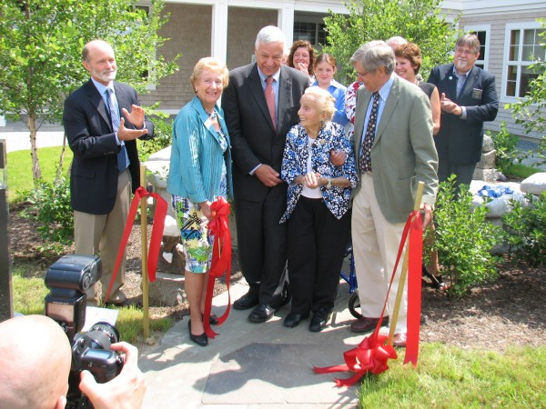 Kathryn W. Davis, 105, is supported by U.S. Rep. Mike Michaud on one side and James Boyer, chairman of the Mount Desert Island Biological Laboratory Board of Trustees, on the other during a building dedication ceremony at the lab on Friday, Aug. 10, 2012. MDI Bio Lab Director Kevin Strange, at left, applauds after Davis cut a ribbon outside the building, which is named in her honor.