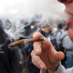 "In an April 20, 2005 file photo, a University of Colorado freshman, who did not want to be identified, joins a crowd smoking marijuana during a ""420"" gathering at Farrand Field at the University of Colorado in Boulder, Colo. People who started using marijuana persistently before age 18 risk losing some of their IQ by the time they're 38, a long-running study says. In contrast, even long-term chronic users who started after age 18 showed no such effect, suggesting the drug holds some particular toxicity for the developing brain."