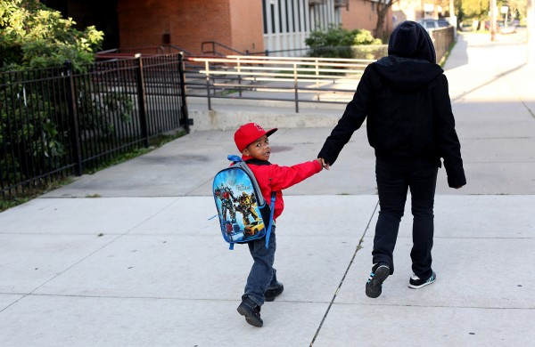A young student gets walked to school at Hefferan Elementary School on the westside in Chicago, Illinois, Wednesday, Sept. 19, 2012, as children returned to school, less than a day after teachers ended a seven-day strike.
