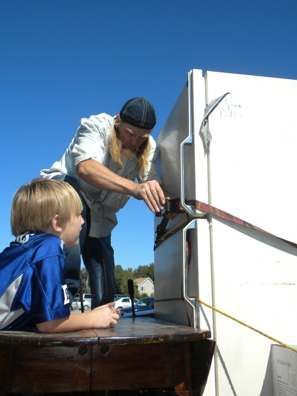 Alan Talgo, who recently purchased a home in Searsport, ties down a refrigerator and other items he acquired Saturday, Sept. 1, 2012, at the Community Church of the Open Door's second annual Great Giveaway in Hampden. His nephew, Matthew Talgo, looks on.