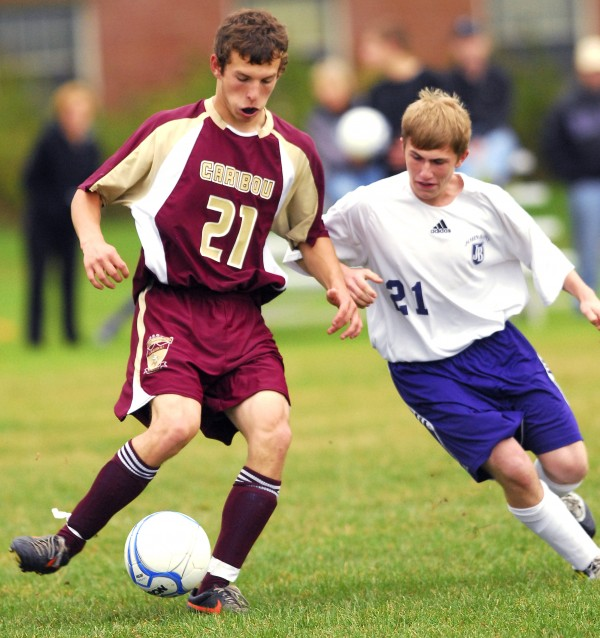 Caribou's Matthew Milliard (21) takes command of the ball ahead of John Bapst's Nate Reese (21) during first-half action at Dixfield in Bangor, Wednesday Sept. 26, 2012.