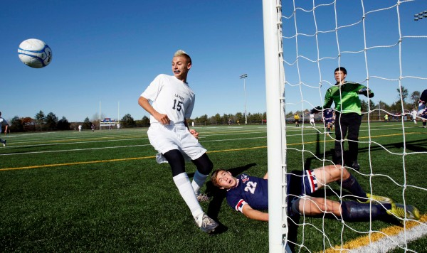 Bangor Christian's Ben Miller ends up on the ground after battling Greenville's Matthew DiAngelo (left) for a corner kick in the Class D soccer state championship in Falmouth in November 2011.
