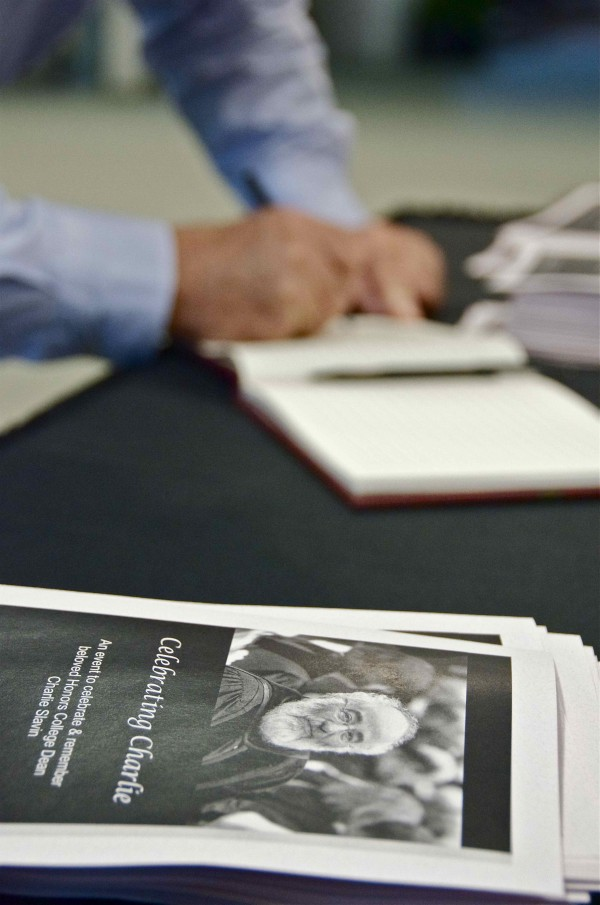 More than 650 people filled the Collins Center for the Arts at the University of Maine Friday, Sept. 14, 2012, to celebrate and remember Honors College Dean Charlie Slavin, who passed away suddenly in July. In this photo, an attendee signs the guestbook.
