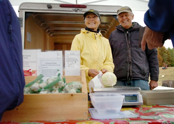 Sarah Lincoln-Harrison (left) and her husband, Richard Harrison, of True North Farms in Liberty help customers at the Common Ground Country Fair in Unity in 2010. The couple are spending their retirement running the MOFGA-certified organic farm.