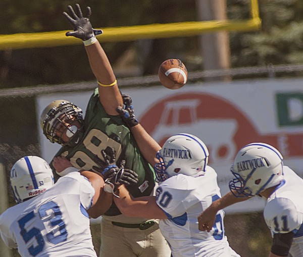 Husson University football player Ernest Wiggins (98) gets off the line of scrimmage to block a pass attempt by Hartwick quarterback Keegan Corbett (11) in the second half of their game at Husson University in Bangor Saturday, Sept. 1, 2012.