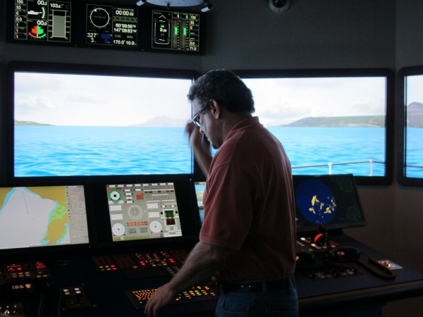 Jim Sanders, a simulation specialist at Maine Maritime Academy, takes the helm of the Bath Iron Works Bridge Simulator at the Castine school.