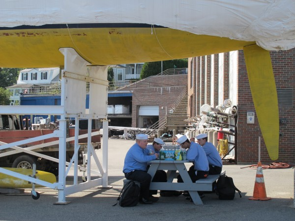 Four students in Maine Maritime Academy's Regiment of Midshipmen eat lunch in the shade provided by a ship at the water's edge in Castine.