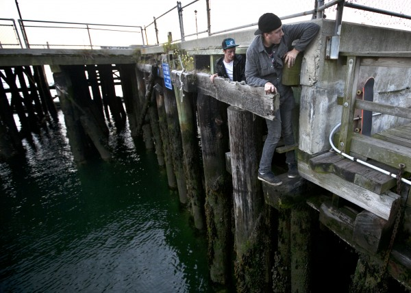 A transient from Pennsylvania and a local man climb out from under the Maine State Pier on Labor Day.