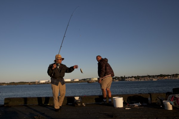 At dusk, a fisherman lands a small catch at the end of the Maine State Pier.