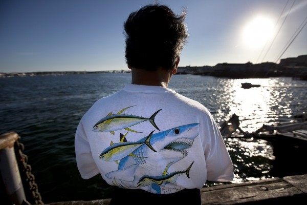 Sharks and tuna are seen on a mackerel fisherman's T-shirt as the sun goes down on Labor Day at the Maine State Pier