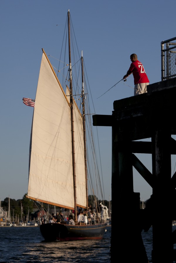 One of three schooners that tie up at the Maine State Pier heads out on an evening sail while a fisherman casts for mackerel.