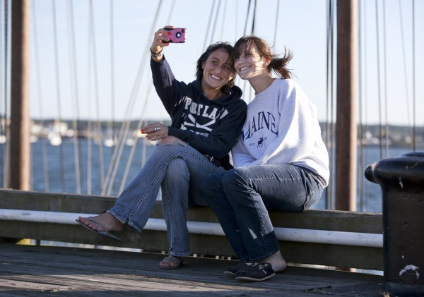 Jessica Grenz, left, of South Dakota and her sister, Julia Grenz, of Missouri, pose for self-portrait while waiting to set sail on a schooner at the Maine State Pier. The chilly evenings that have arrived with the unofficial end of summer prompted the sisters to buy souvenir sweatshirts.