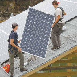 Brandon Bernard, left, and Joe Maisonave carry one of 44 photovoltaic solar collection panels toward its place in a solar array on the roof of Reversing Falls Lobster Wharf in Harpswell recently. Each panel weighs about 44 pounds and can harness 240 watts of energy.
