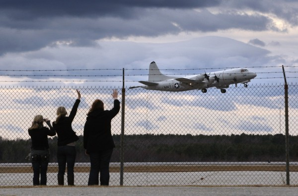 In this Saturday, Nov. 28, 2009 file photo, Nicole Underwood (from left), Palen Raspet and Lisa Zwierko wave goodbye as the last P3 Orion takes off on its final flight from Brunswick Naval Air Station in Brunswick, Maine.