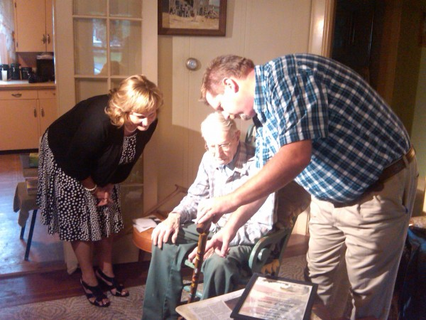 Maine's first lady Ann LePage (left) presents Westbrook resident and World War II veteran Milton Gowen, 94, with an eagle cane on Tuesday, Sept. 4, 2012, to honor his time in military service. The cane was carved by Andy Rice (right), who engraved Gowen's name and military branch on the walking stick.