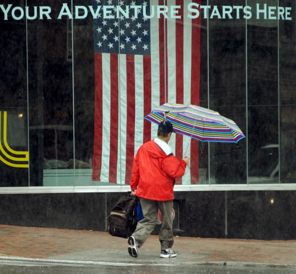 A pedestrian passes in front of Epic Sports in downtown Bangor in the rain on Wednesday morning, Sept. 5, 2012. Heavy rainfall dropped over 1.5 inches of rain in the Bangor area, according to The Weather Channel.