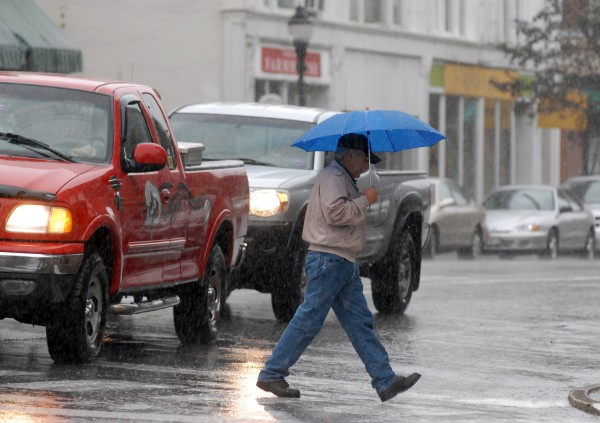 A pedestrian crosses Central Street in downtown Bangor Wednesday morning, Sept. 5, 2012. Heavy rainfall dropped over 1.5 inches of rain in the Bangor area, according to The Weather Channel.