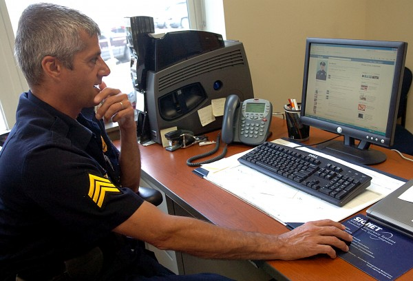 Sgt. Paul Edwards of the Bangor Police Department looks over law enforcement Facebook pages in August 2011.