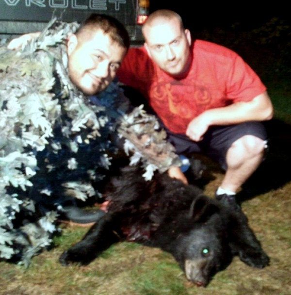 Two days into their five-day hunt, Jesse Luera (left) of Killeen, Texas, was the first to bag a black bear as five veterans of the wars in Iraq and Afghanistan found some civilian rest and recreation in the woods of Washington County under the sponsorship of the Wounded Warrior Project. Posing with Luera and the bear is Louis Doyon of Lewiston, the only bow hunter in the group.