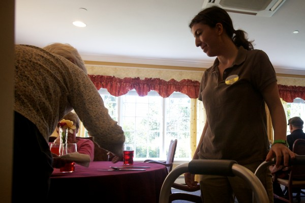 Tovah Abrams hangs on to Barbara Champeon's walker as she stands after lunch at Cape Memory Care in Cape Elizabeth on Thursday, Sept. 27, 2012.