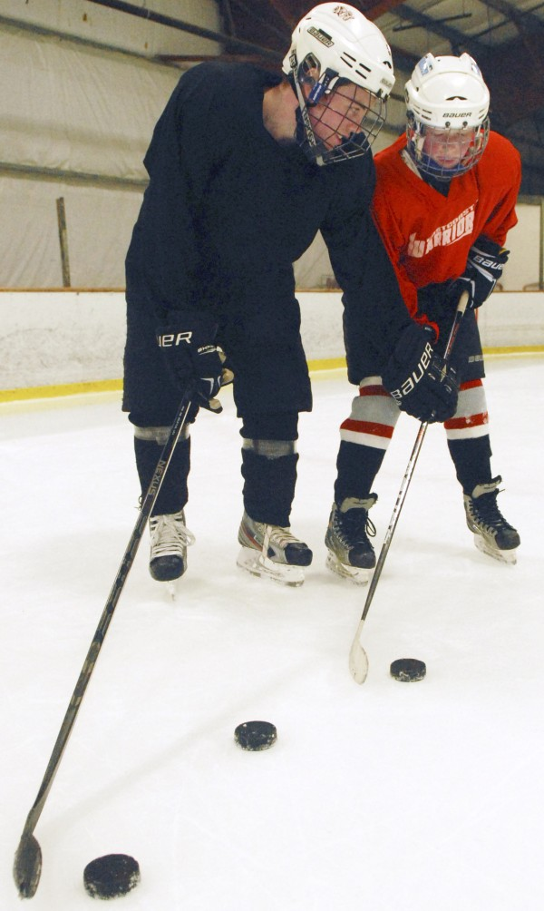 Cameron Dickson explains some skills to a younger player during a pratice session at Penobscot Ice Arena in Brewer on Thursday, Sept. 20 2012.