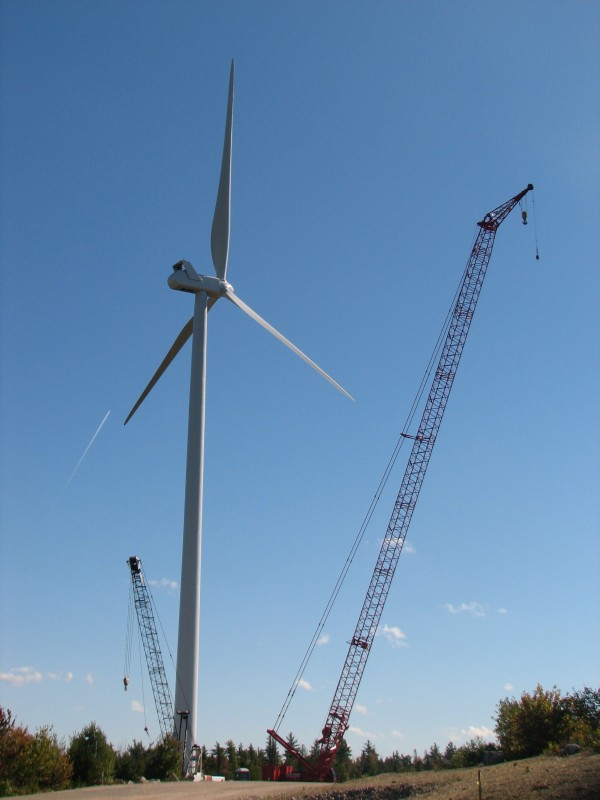 A turbine 476 feet tall at the tip of its upright blade towers over construction cranes and trees in Township 16 in eastern Hancock County on Tuesday, Sept. 25, 2012. It is one of 19 turbines recently erected in Township 16 by First Wind. The company hopes to have the turbines generating electricity and connected to the regional distribution grid by the end of October, according to a First Wind official.