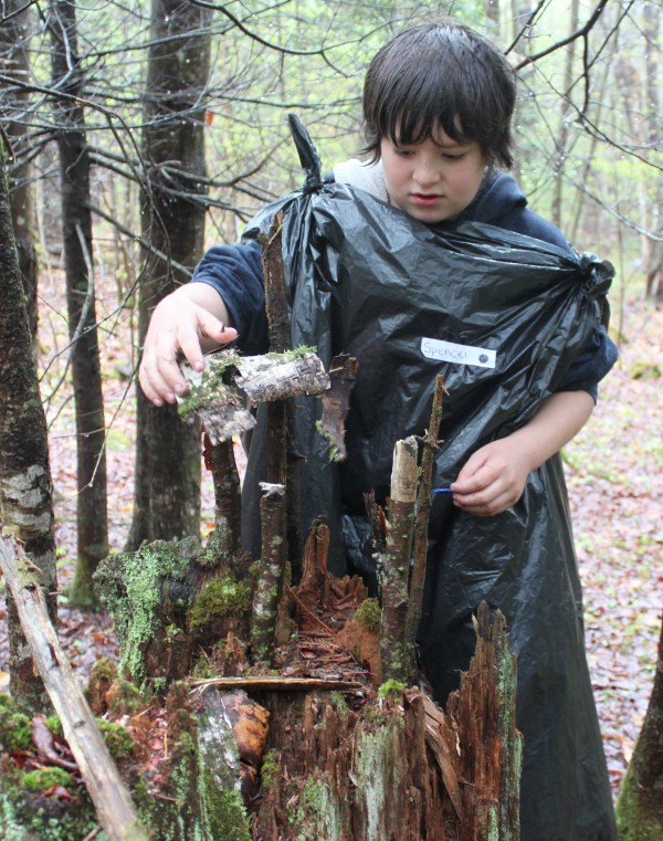 Fourth-grader Spencer Black builds a fairy house out of fallen birch bark and twigs in the forest beside Brownville Elementary School on May 10, 2012, during the school's first &quotNature Trail Celebration Day.&quot He and the rest of the student body spent the day outdoors, exploring their revamped interpretive nature trail.
