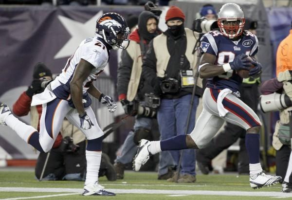 Denver Broncos cornerback Andre Goodman (21) tries to stop New England Patriots wide receiver Deion Branch (84) as he scores on a 61-yard touchdown during the first half of an NFL divisional playoff football game Jan. 14, 2012, in Foxborough, Mass.