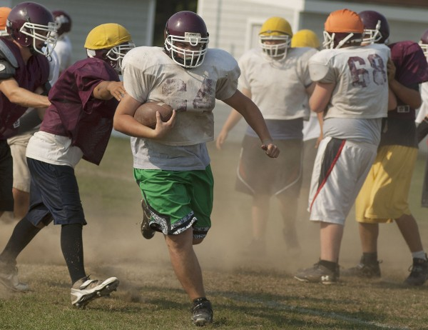Nokomis football players go through play drills at practice in Newport in August.