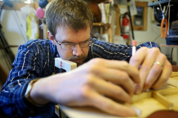 Carter Ruff, luthier and proprietor of Subterranean Music Works in Bath, marks a brace before carving it on the backside of a guitar top Monday ,Sept. 24, 2012. Ruff is making a guitar from a surviving pew from his church that burned down last year.