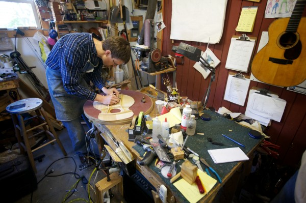 Carter Ruff, luthier and proprietor of Subterranean Music Works in Bath, marks a brace before carving it on the backside of a guitar top Monday, Sept. 24, 2012. Ruff is making a guitar from a surviving pew from his church that burned down last year.